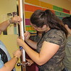 Staff photo by Cathy Spaulding<br /> Hilldale High School teacher Marla Walkup helps students measure paper for a homecoming door decoration. She returned to the classroom this year after a six-year absence.