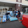 Staff photo by Wendy Burton<br /> Victor Lezama, left, Jeanne Hayden and Sam Cox, both from the Subway at Arrowhead Mall, unload water in the parking lot of PC Landing Zone on Wednesday evening. Several businesses and schools began collecting items to take to areas ravaged by Hurricane Harvey in Texas. Southern Material brought a forklift to load more than 18 pallets of water and drinks donated by Anheuser Busch, Wal-Mart, and other businesses and individuals on Wednesday. Donations continue to be accepted at PC Landing Zone, Bacone College, Okie Country 101.7 and Max's Garage. The truck will leave for Texas on Friday afternoon.