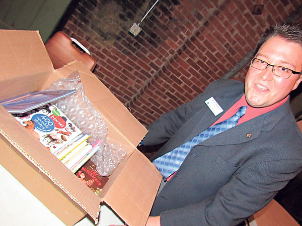 CATHY SPAULDING/Muskogee Phoenix<br /> Brian Jackson with Junior Achievement of Oklahoma shows a box of surplus Library of Congress children's books donated to Muskogee Public Schools on Thursday.