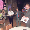 CATHY SPAULDING/Muskogee Phoenix<br /> Muskogee School Superintendent Dr. Jarod Mendenhall, right shows one of the surplus children's books Muskogee Public Schools received Thursday from the Library of Congress. The books were presented by Muskogee City Council member Ivory Vann, third from left and Junior Achievement of Oklahoma Development Manager Brian Jackson.