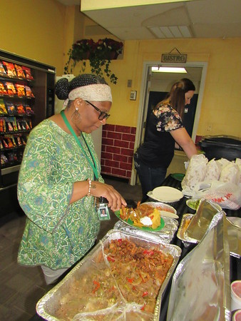 Sadler Arts Academy fourth-grade teacher Carol Nunley, left, and librarian Amanda Cumbey help themselves to Mexican food after being honored at an assembly Friday.