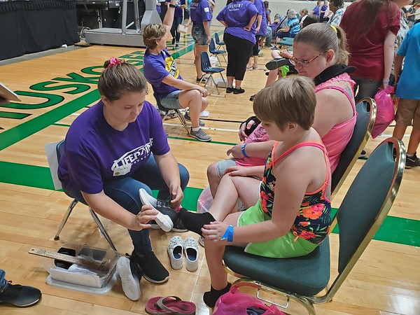 CHESLEY OXENDINE/Muskogee Phoenix<br /> Chrissy Shields waits while her daughter Alyssa tries on shoes with the help of Bailey Esterline, left, at the Our Kids Better Together giveaway event at the Muskogee Civic Center on Saturday.