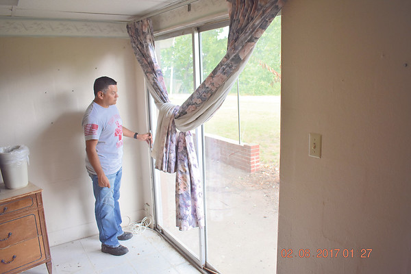Staff photo by Mark Hughes<br /> Victor Lezama, creator of The Barracks, looks out a sliding glass door that exits to a patio. The Barracks will house homeless veterans, couples and families with the caveat that they attend classes sponsored by The Barracks that will assist them in obtaining a job.