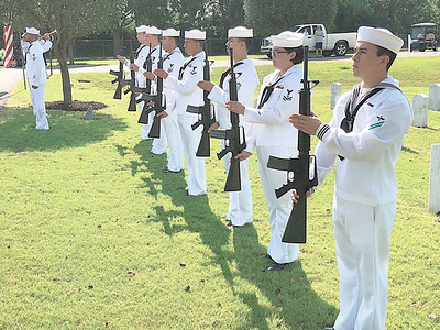 CHESLEY OXENDINE/Muskogee Phoenix An Oklahoma City rifle team provided a three-volley salute during the funeral of Seaman First Class Eugene Wicker.