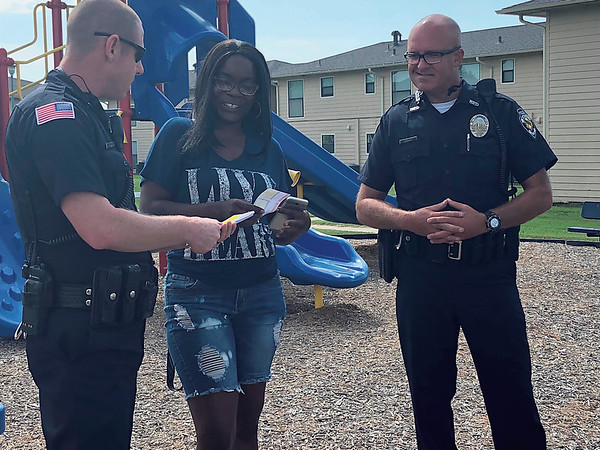 CHESLEY OXENDINE/Muskogee Phoenix<br /> Muskogee Police officers Jody Standridge, left, and Danny Spears, right, gives Mona Vanhook a Salvation Army food voucher.