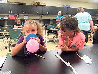 CATHY SPAULDING/Muskogee Phoenix Camaya Renshaw, left, blows a balloon while her mechanical engineering teammate, BrenLee Morgan, observes. The two used the balloons to make a hovercraft as part of an All Girls Engineering Camp being conducted this week at Muskogee High School.