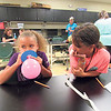 CATHY SPAULDING/Muskogee Phoenix<br /> Camaya Renshaw, left, blows a balloon while her mechanical engineering teammate, BrenLee Morgan, observes. The two used the balloons to make a hovercraft as part of an All Girls Engineering Camp being conducted this week at Muskogee High School.