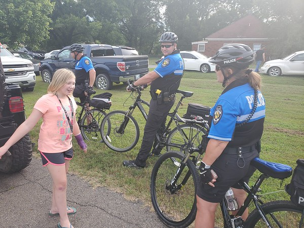 CHESLEY OXENDINE/Muskogee Phoenix<br /> (From left) Gracie Ayers chats with Muskogee Police Officers James Hamlin, Todd Cumbey and Lynn Hamlin during the Okies Neighborhood National Night Out.