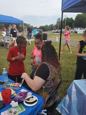 CHESLEY OXENDINE/Muskogee Phoenix<br /> Demareante Wooten looks on as his cousin Genesis Ousley gets her face painted by Autumn Lee during the Okies Neighborhood National Night Out.