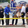 Staff photo by Mark Hughes<br /> Muskogee Police Chief Rex Eskridge, left, watches as investigators collect evidence at a scene of an officer-involved shooting just west of 32nd Street on Broadway early Monday morning. The man who was shot was taken to the hospital. No names have been released.