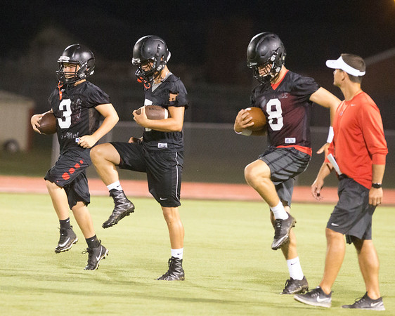 Phoenix special photo by Von Castor<br /> Hilldale football coach Chad Kirkhart, far right, watches the Hornet quarterbacks Johnnie Durossette, left, Dawson Neighbors, center, and Jaron Nail warm up during the first fall practice session on Monday. The Hornets took the field at 12:01 a.m. and returned at 4 p.m.