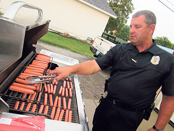 CATHY SPAULDING/Muskogee Phoenix Fort Gibson Police Chief Donnie Yarbrough cooks hot dogs outside the Frank Gladd American Legion Post 20, where the Fort Gibson National Night Out event was being held.