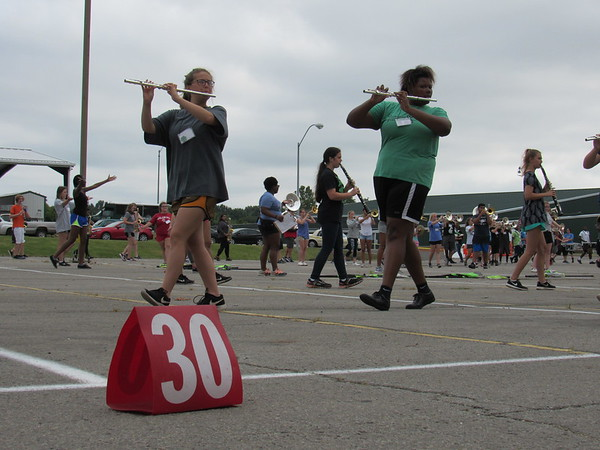 Staff photo by Cathy Spaulding<br /> Muskogee High School flutists and clarinetists pass each other during marching band practice Monday.