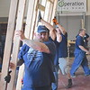Staff photo by Mark Hughes<br /> Garrett Quinn, a Navy veteran, helps move a section of a tiny house Friday they helped build at the Indian Capital Technology Center. Members of the Oklahoma Volunteers Project coordinated the effort that resulted in a 300-square-foot home being built for a local homeless veteran.