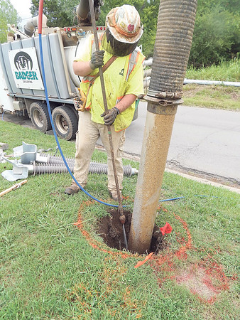 Sebastian Rindels with Badger Daylighting sprays water into a hole being dug Wednesday along 24th Street. Worker Zach Pritchard said water is sprayed at high pressure into a hole. A tube sucks the mud out. The company is digging holes for new OG&E power poles along 24th Street.