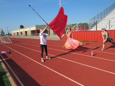 CATHY SPAULDING/Muskogee Phoenix Hilldale sophomore Autumn Pohlschneider, left practices a flag routine with help from color guard member Angel Clark, center, and senior Isabella Morrow.