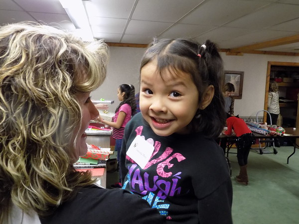 Special photo by Mike Elswick<br /> Nereida Mata, 5, was all smiles at the conclusion of her shopping excursion at The Joy of Giving Shoppe as volunteer Susan Wiebe gets a big hug.