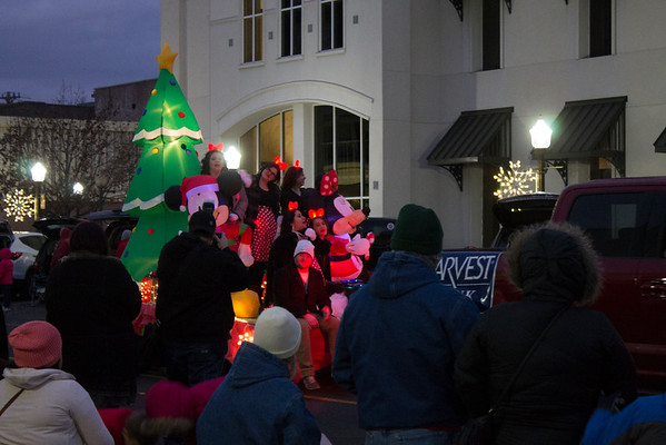Special photo by Wendy Burton<br /> The Arvest Bank float featured Mickey and Minnie Mouse along with a group of singers with glowing bows at the Muskogee Christmas Parade on Saturday.