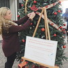 Staff photo by Mark Hughes<br /> Stephanie Palmer decorates the Tree of Remembrance at Arrowhead Mall. Her mother, Pamela Stonebarger, started what she hopes will be an annual Christmas event that commemorates the lives and deaths of Oklahoma murder victims.
