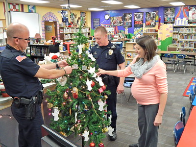 Staff photo by Mark Hughes Hilldale upper elementary Resource Officers Danny Spears and Nick Ford, along with school counselor Anelicia Brimacomb, sort through the more than 80 angel requests hanging on the school's tree. Not only do school children have individual angels, but their siblings have their angels also.