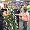 Staff photo by Mark Hughes<br /> Hilldale upper elementary Resource Officers Danny Spears and Nick Ford, along with school counselor Anelicia Brimacomb, sort through the more than 80 angel requests hanging on the school's tree. Not only do school children have individual angels, but their siblings have their angels also.