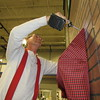 Staff photo by Cathy Spaulding<br /> Mike Calavan attaches an awning to one of the shops in Christmas Village. First Baptist Church will open the village next Tuesday through Friday.