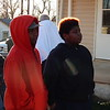 Staff photo by Cathy Spaulding<br /> Brothers Mychael Carter, 13, second left, and Sean Carter, 10, right, watch firefighters put out a house fire. The boys had just helped their neighbors, Juanita Craig, left, and Tony Terry, back turned, get away from the house.