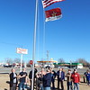 Staff photo by Mark Hughes<br /> Army veteran John Weeden raises an American flag Thursday during a ceremony in Okay commemorating the town's Veterans Monument. The monument lists 195 Okay residents who served from the Civil War to those on active duty.