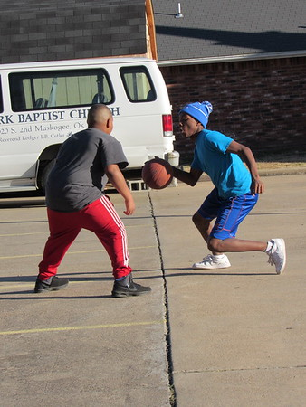 Staff photo by Cathy Spaulding<br /> Marquez Barnett, right, tries to dribble past Lashawn Manns while playing basketball Friday at St. Mark Baptist Church. They enjoyed one of the final days of holiday break. They and other Muskogee Public School students return to class Monday.