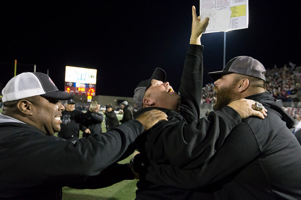 Special photo by Von Castor<br /> Wagoner head coach Dale Condict, center, celebrates with assistant coach Chad Soma, right, and Jamie Powell seconds after Wagoner won its second straight 4A football championship Friday night in Owasso.