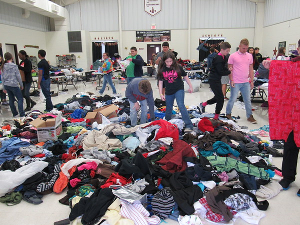 Staff photo by Cathy Spaulding<br /> Warner High School and seventh-grade students sort through mounds of clothing purchased for and donated to the school's Christmas charity. Warner also plans a community Christmas Festival.