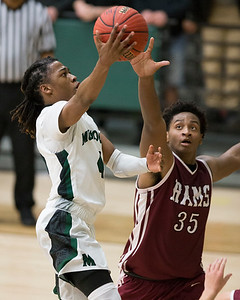 Phoenix special photo by Von Castor Muskogee's Tyreece Berry, left, scores one of his two baskets in overtime ahead as Owasso's Josh Proctor defends Tuesday at Ron Milam Gymnasium. The Roughers beat the Rams 65-64.