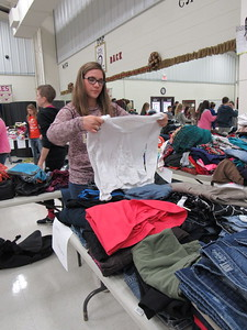 Staff photo by Cathy Spaulding Warner High School student Jalynn Duncan folds clothes for the school's Christmas charitable program. The school also plans a Christmas Festival next Wednesday.