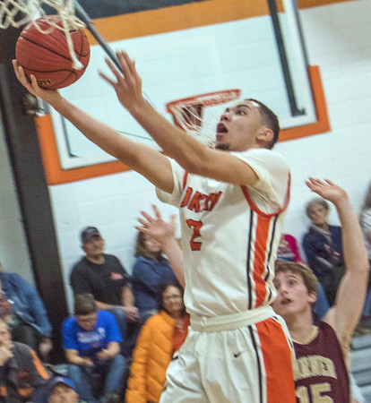 Phoenix special photo by John Hasler<br /> Okay's Caleb Riggs drives for the basket while defended by Warner's Bobby Ward in Tuesday's game at Okay.