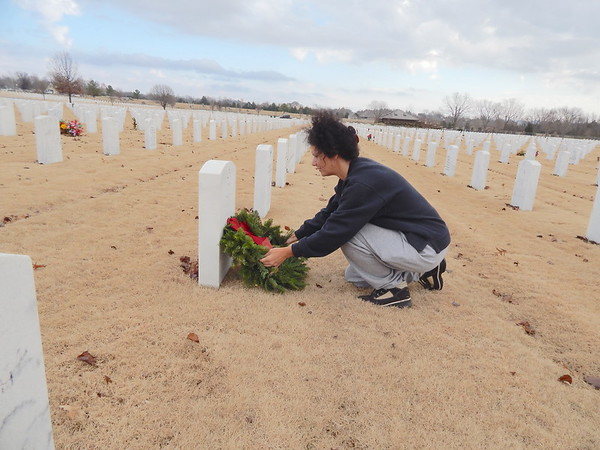 Staff photo by Mark Hughes A volunteer lays a live wreath at the headstone of a veteran at Fort Gibson National Cemetery during a Wreaths Across America event. This year, live wreaths will be placed on gravesites by families, friends and volunteers at national cemeteries around the world at 11 a.m. Dec. 17.