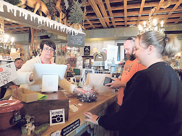 KENTON BROOKS/Muskogee Phoenix<br /> Stacy Burns, owner of Hattie's House, rings up items for Andy and Tiffany Greene during Small Business Saturday.