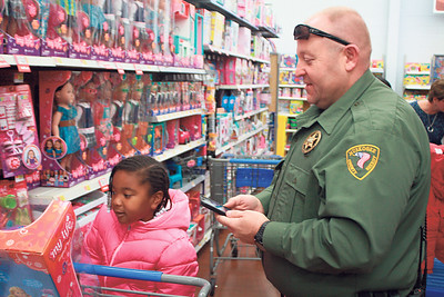 Special photo by Chesley Oxendine Muskogee County Reserve Deputy Alan Foster helps Niyla Holmes, 5, pick out toys during the Shop With the Sheriffs event at Wal-Mart.