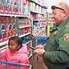 Special photo by Chesley Oxendine<br /> Muskogee County Reserve Deputy Alan Foster helps Niyla Holmes, 5, pick out toys during the Shop With the Sheriffs event at Wal-Mart.