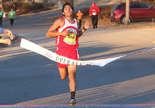 Phoenix special photo by John Hasler Jess Mandalen of Bacone College crosses the line in 16 minutes, 24 seconds to win the men's portion of the Garden of Lights 5K run at Honor Heights Park.