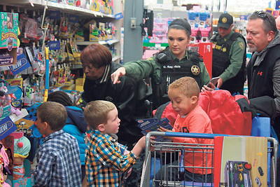 Special photo by Chesley Oxendine Muskogee County sheriff's deputies help children choose toys during Shop with a Sheriff event at Wal-Mart on Saturday.