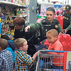 Special photo by Chesley Oxendine<br /> Muskogee County sheriff's deputies help children choose toys during Shop with a Sheriff event at Wal-Mart on Saturday.