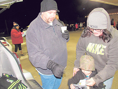 CATHY SPAULDING/Muskogee Phoenix  First Baptist Church of Fort Gibson Pastor Nate Capps helps Liz Meissner and her son Ryker get some gloves before the Fort Gibson Christmas parade Monday night.