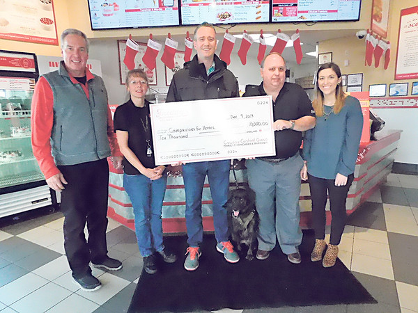 KENTON BROOKS/Muskogee Phoenix<br /> Mark Thompson, second from right, presents a check for $10,000 from Freddy's Frozen Custard and Steakburgers to David Sharpe of Companion for Heroes.