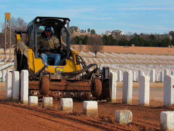 CATHY SPAULDING/Muskogee Phoenix<br /> A contractor does sodding work between headstones at Fort Gibson National Cemetery earlier this month. Contractors resodded older parts of the cemetery.
