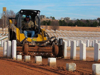 CATHY SPAULDING/Muskogee Phoenix A contractor does sodding work between headstones at Fort Gibson National Cemetery earlier this month. Contractors resodded older parts of the cemetery.