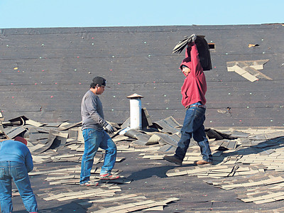 CATHY SPAULDING/Muskogee Phoenix Roof workers carry shingles and other debris from a roof at Keetoowah Village Apartments on Monday. Keetoowah Village Apartment complex, at North York Street and Harris Road, is replacing the roofs on eight buildings. Thomas Brothers did the roofing as a subcontractor for Eagle Vision.