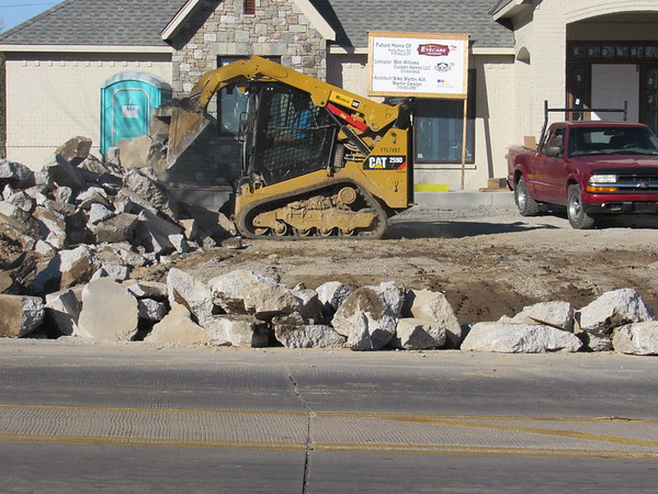 Staff photos by Cathy Spaulding A front-end loader deposits concrete chunks in front of an optometrist's new office Monday. Contractors were cutting a curb. Westbound traffic on Chandler Road was down to one lane west of York Street on Monday. Optometrist Dr. Karla Rice is moving her practice, Eyecare of Muskogee, from York Street to Chandler Road. She said the relocated practice will open by Jan. 31.