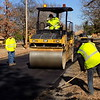 Staff photo by Mike Elswick<br /> Muskogee County workers are seen Tuesday working on applying new asphalt to River Ridge Road at the north end of North Woodland Road. On Thursday, the work will shift to North Woodland Road, which will need to be closed for at least a couple of hours midday, said District 1 County Commissioner Ken Doke.