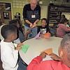 Staff photo by Cathy Spaulding<br /> Retired service manager Dan Lutz shows Cherokee Elementary second-graders how to fold paper squares into paper cups on Monday.