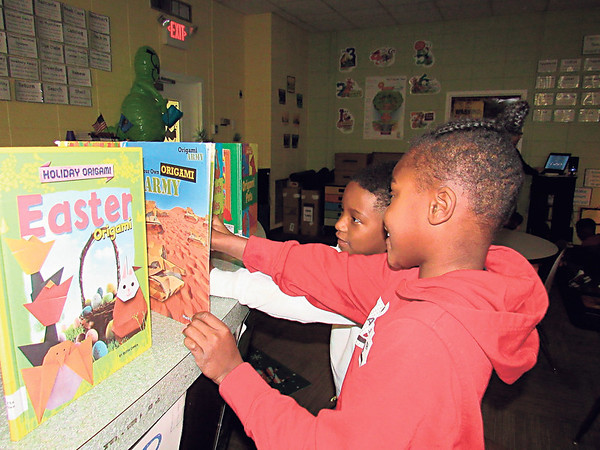 Staff photo by Cathy Spaulding<br /> Cherokee Elementary second-graders Kerionn Wagner, left, and Dominik Riggins study a book about origami after learning about the folded paper craft on Monday.